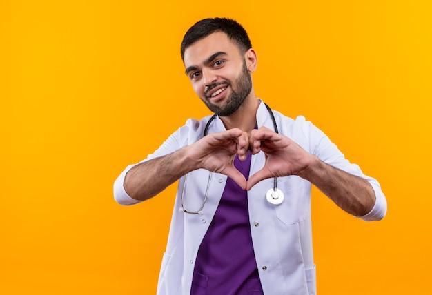 Jovem médico satisfeito com um estetoscópio, jaleco, mostrando um gesto de coração em fundo amarelo isolado