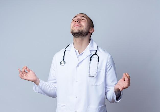 Jovem médico satisfeito, vestindo túnica médica e estetoscópio em volta do pescoço, meditando com os olhos fechados, isolado na parede branca