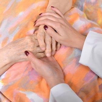 Jovem médico segura a mão da velha