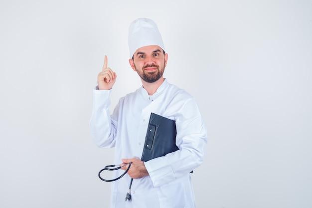 Jovem médico segurando a prancheta, estetoscópio, apontando para cima em uniforme branco e parecendo inteligente. vista frontal.