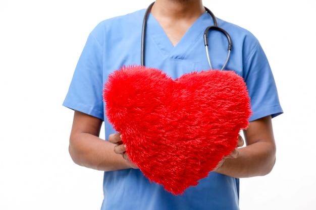 Jovem médico segurando um lindo coração vermelho na mão