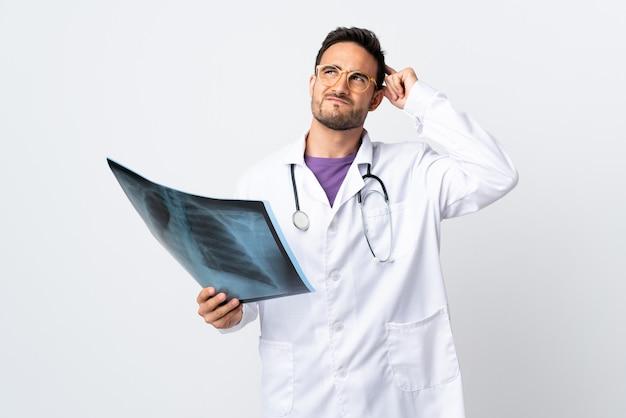 Jovem médico segurando uma radiografia isolada no fundo branco, tendo dúvidas e com expressão facial confusa