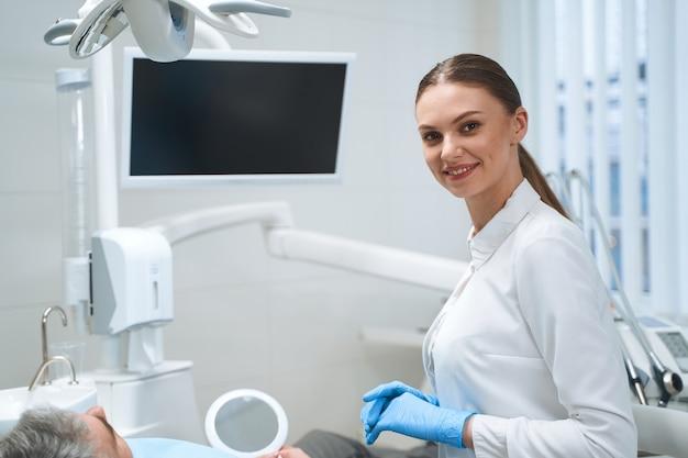 Jovem médico sorridente de uniforme branco está de pé no escritório ao lado de uma tela digital enquanto trata de um homem