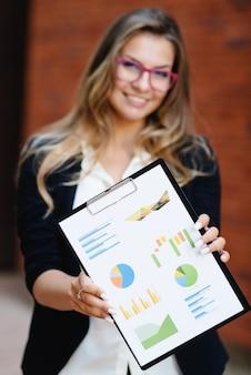 Jovem médico sorridente feliz, mostrando a pasta com infográficos