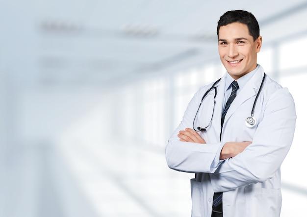 Jovem médico sorridente no fundo desfocado do hospital. bokeh