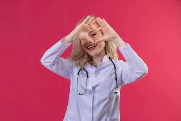 Jovem médico sorridente usando estetoscópio em bata médica, mostrando um gesto de coração em backgroung vermelho