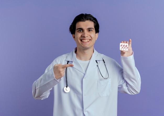Jovem médico sorridente, vestindo túnica médica e estetoscópio, mostrando um pacote de cápsulas médicas apontando para ele isolado na parede roxa