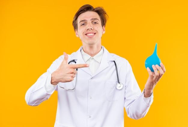 Jovem médico sorridente, vestindo túnica médica, segurando um estetoscópio e apontando para um enema isolado na parede laranja