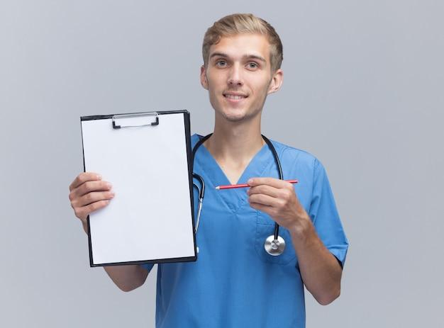 Jovem médico sorridente, vestindo uniforme de médico, segurando um estetoscópio e apontando com um lápis para uma prancheta isolada na parede branca