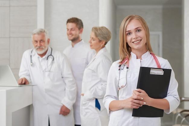 Jovem médico sorrindo, equipe médica posando para trás.