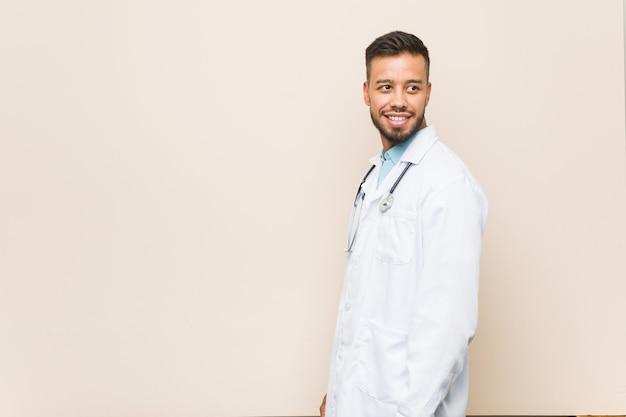 Jovem médico sul-asiático olha de lado sorrindo, alegre e agradável.