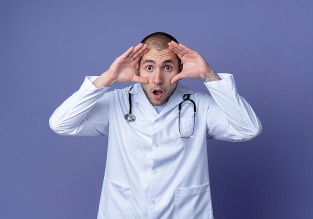 Jovem médico surpreso, vestindo túnica médica e estetoscópio no pescoço, fazendo grandes olhos isolados na parede roxa