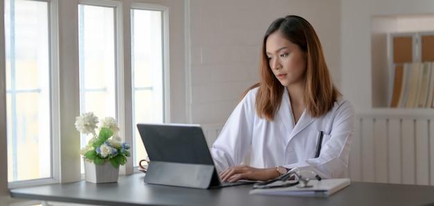 Jovem médico trabalhando em registros médicos com tablet no escritório do hospital