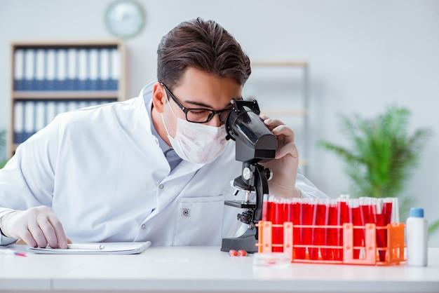 Jovem médico trabalhando no laboratório com microscópio