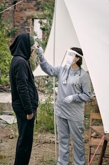 Jovem médico uniformizado medindo a temperatura do refugiado