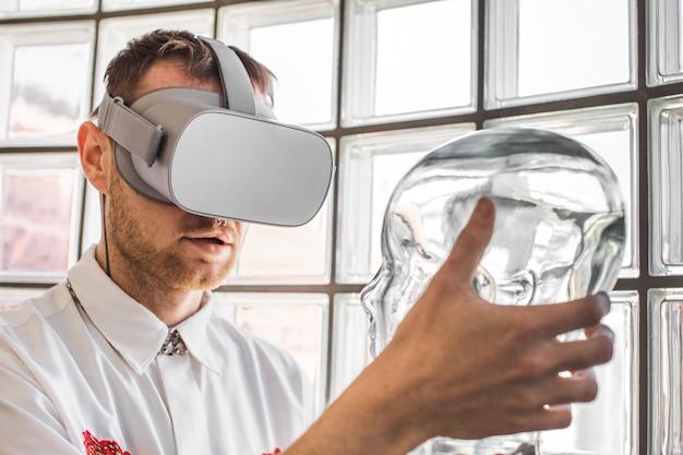 Jovem médico usando óculos de realidade virtual, examinando um manequim na simulação de realidade virtual