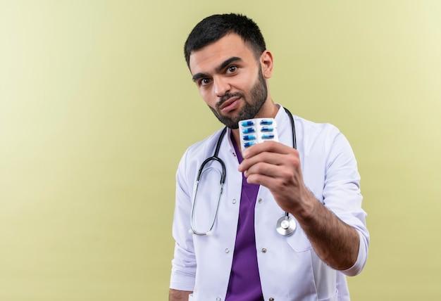 Jovem médico vestindo bata médica e estetoscópio segurando comprimidos na parede roxa isolada