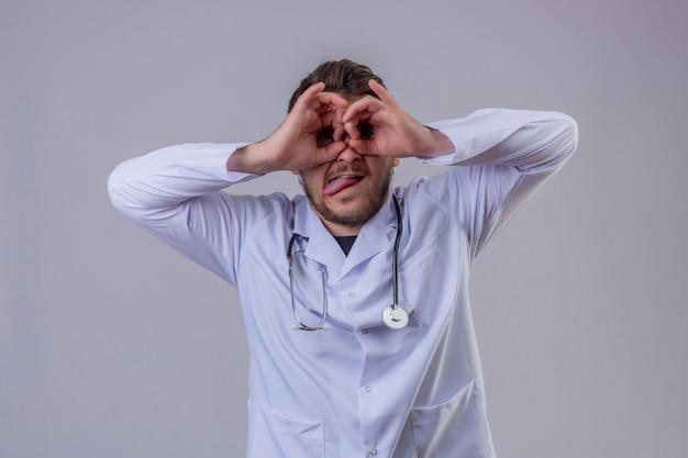 Jovem médico vestindo jaleco branco e estetoscópio fazendo okey gesto como binóculos furando a língua de fora, olhando por entre os dedos, expressão maluca