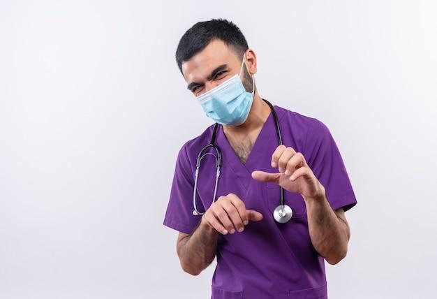 Jovem médico vestindo roupas roxas de cirurgião e máscara médica com estetoscópio mostrando gesto de tigre em parede branca isolada