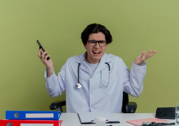 Jovem médico zangado, sentado à mesa, vestindo bata médica e estetoscópio com óculos