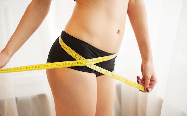 Jovem medindo a cintura com fita adesiva