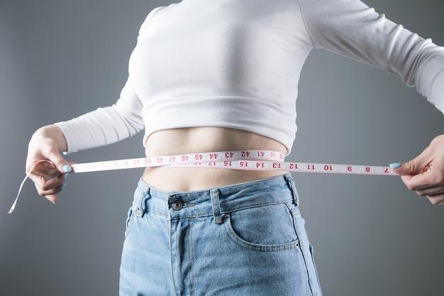 Jovem medindo a circunferência abdominal em uma parede cinza