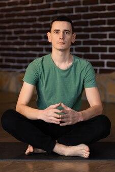 Jovem meditando com os olhos abertos e as mãos em posição de oração