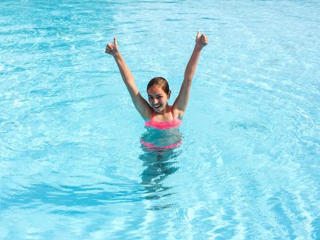 Jovem menina adolescente nada e se divertir na piscina ao ar livre