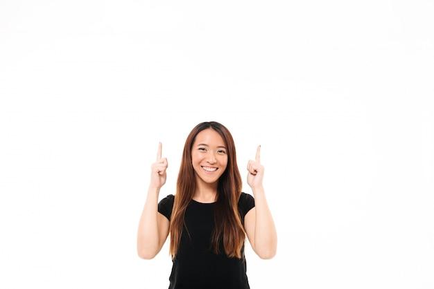 Jovem menina asiática alegre em camiseta preta, apontando com dois dedos para cima, olhando para a câmera