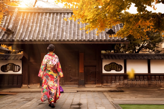 Jovem menina asiática andando e vestindo quimono