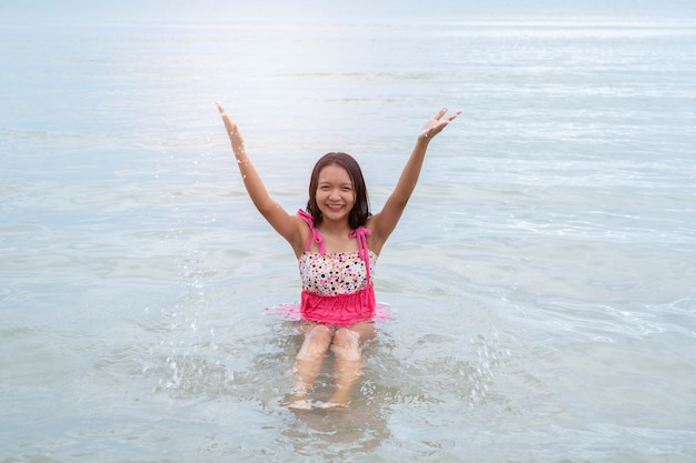Jovem menina asiática brincando no mar.
