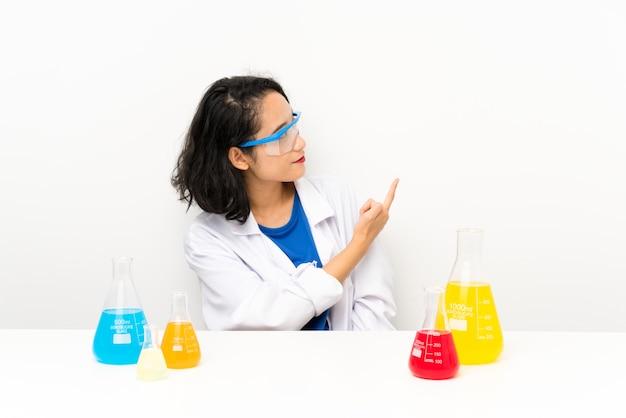 Jovem menina asiática científica apontando para trás com o dedo indicador