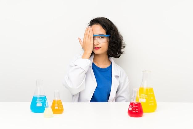 Jovem menina asiática científica cobrindo um olho à mão