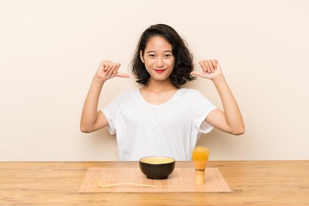 Jovem menina asiática com chá matcha orgulhoso e satisfeito