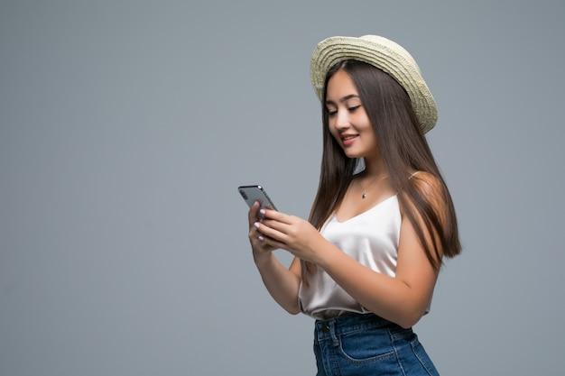 Jovem menina asiática com chapéu de palha usar telefone em fundo cinza