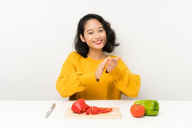 Jovem menina asiática com legumes em uma mesa aplaudindo