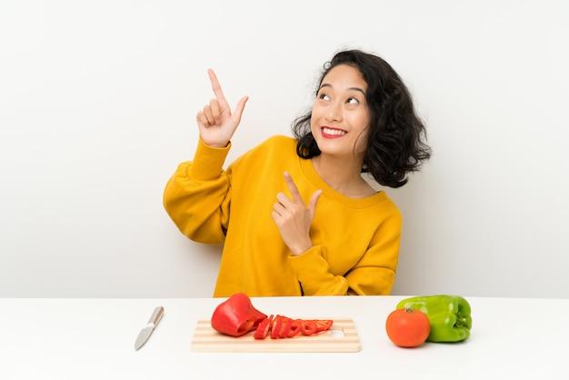 Jovem menina asiática com legumes em uma mesa apontando com o dedo indicador uma ótima idéia