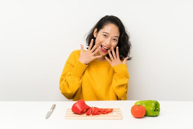 Jovem menina asiática com legumes em uma mesa com expressão facial de surpresa