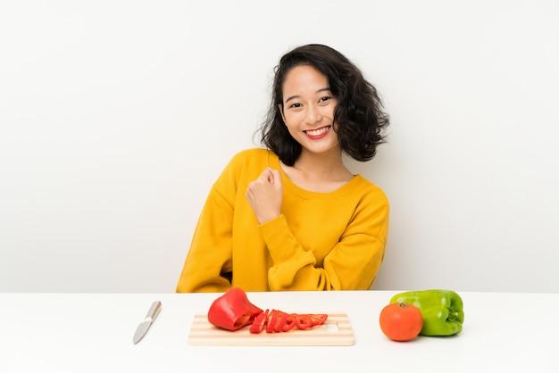 Jovem menina asiática com legumes em uma mesa comemorando uma vitória