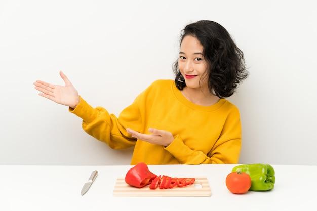 Jovem menina asiática com legumes em uma mesa, estendendo as mãos para o lado por convidar para vir