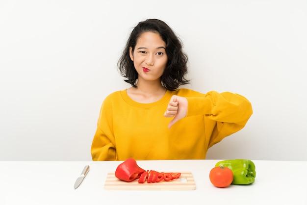 Jovem menina asiática com legumes em uma mesa mostrando o polegar para baixo o sinal