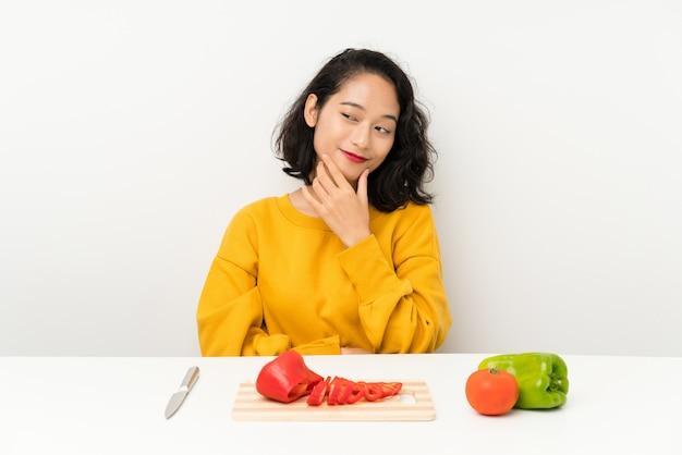Jovem menina asiática com legumes em uma mesa, pensando em uma idéia