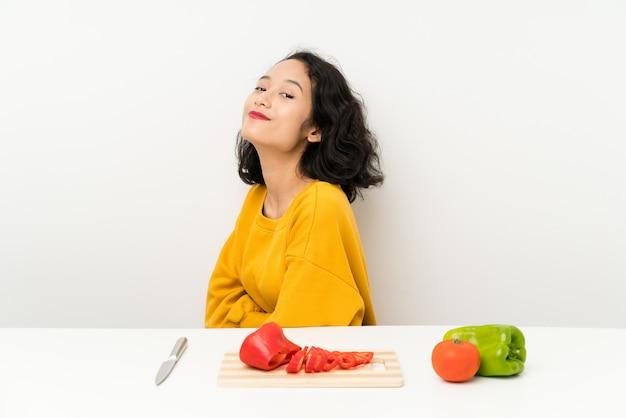Jovem menina asiática com legumes em uma mesa rindo