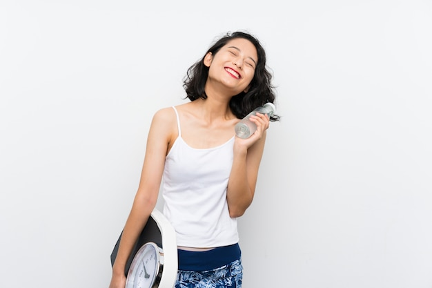 Jovem menina asiática com máquina de pesagem sobre parede branca isolada