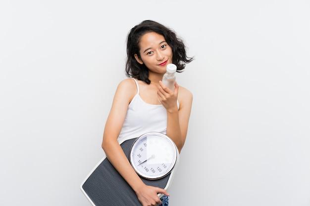 Jovem menina asiática com máquina de pesar sobre fundo branco isolado