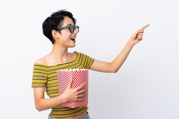 Jovem menina asiática com óculos 3d e segurando um grande balde de pipocas enquanto apontando para fora