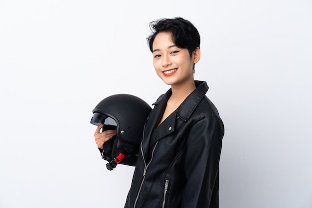 Jovem menina asiática com um capacete de moto sobre parede branca isolada, sorrindo muito