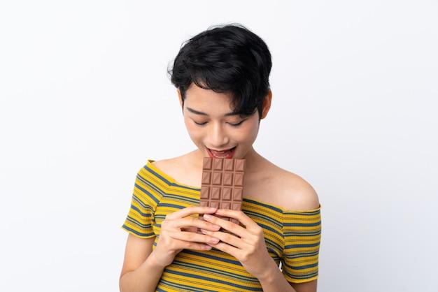 Jovem menina asiática comendo uma tablete de chocolate
