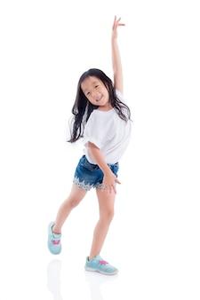 Jovem menina asiática dançando e sorri sobre fundo branco