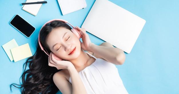 Jovem menina asiática deitada em azul com laptop, smartphone, fones de ouvido e nota em torno de azul
